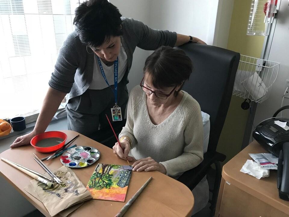 La patiente est en train de peindre, sous l'oeil attentif de Fabienne Roques