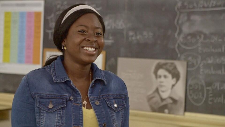 Une jeune femme souriante, avec en arrière-plan le tableau noir de la classe