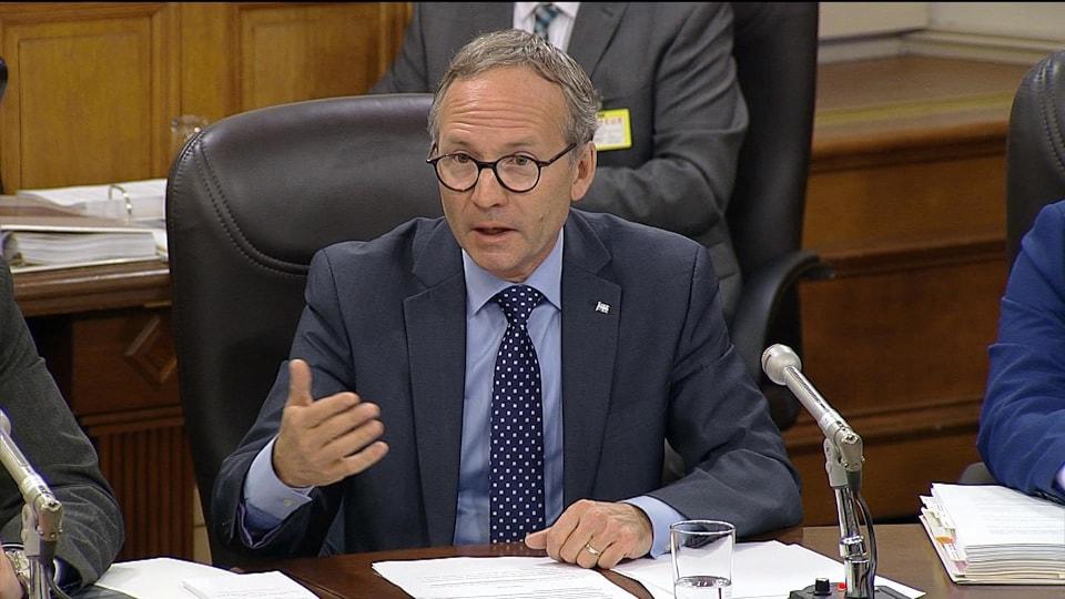 Le ministre de la Sécurité publique du Québec, Martin Coiteux, assis à une table de conférence.