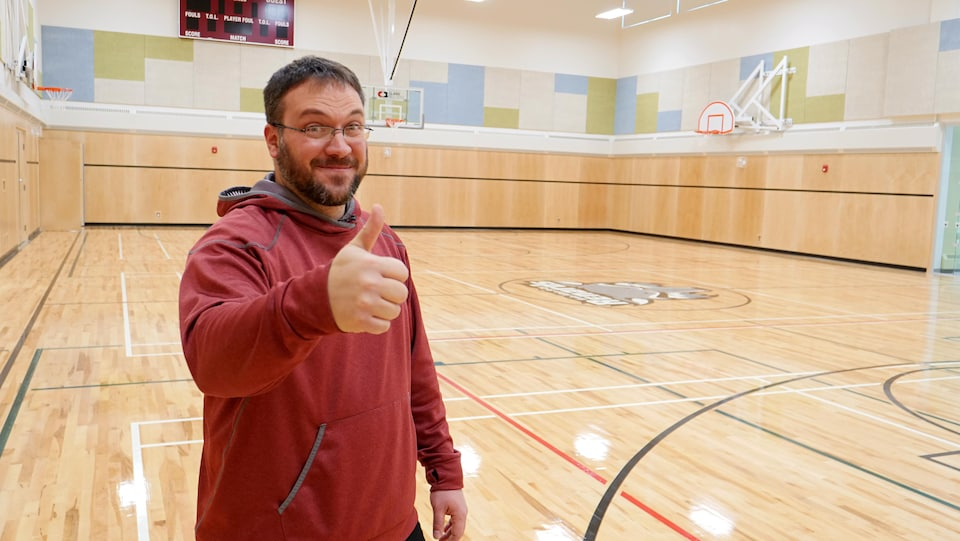 Un homme donne un pouce d'approbation dans un gymnase.