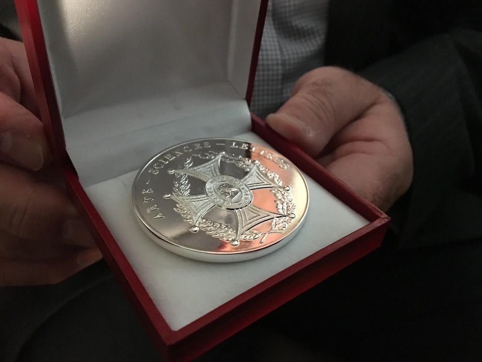 Une médaille en argent se trouve dans une petite boite.