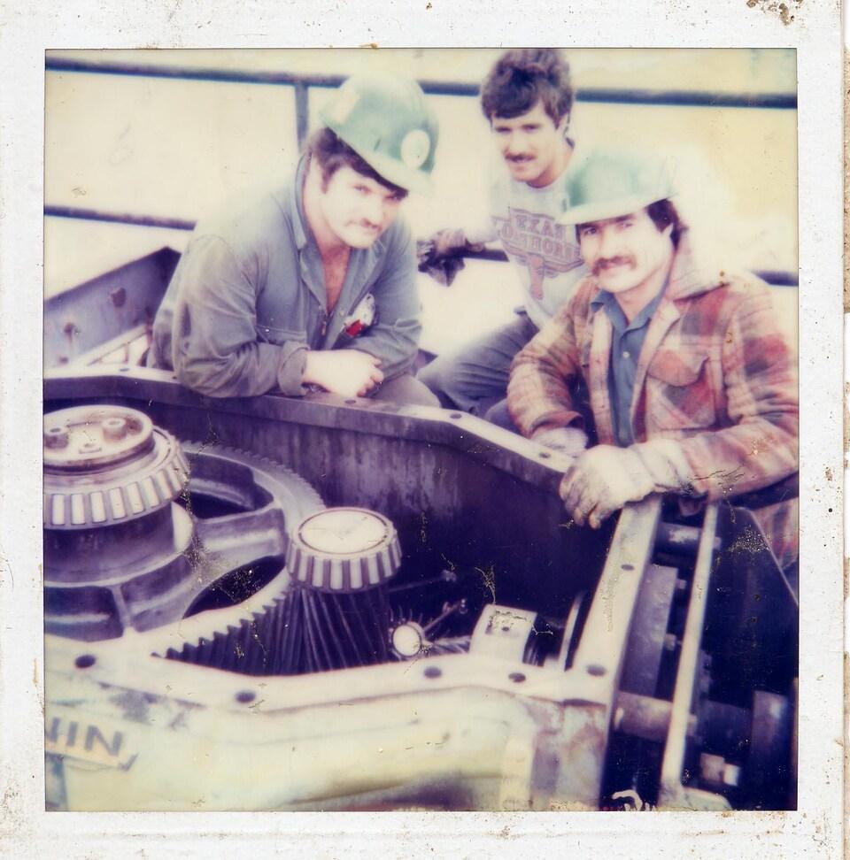 Trois travailleurs à l'usine de pâte et papier d'Edmundston.