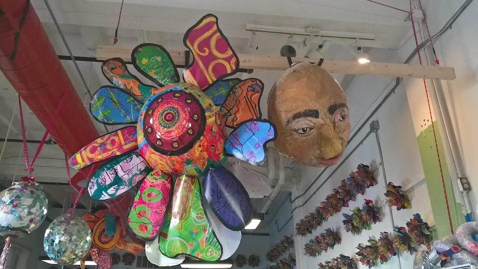 Un énorme masque et une grande «fleur officielle d'Athens» accrochés au plafond de l'atelier Passion Works