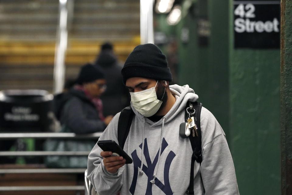 Un homme porte un masque sanitaire et consulte son téléphone mobile dans le métro de New York.