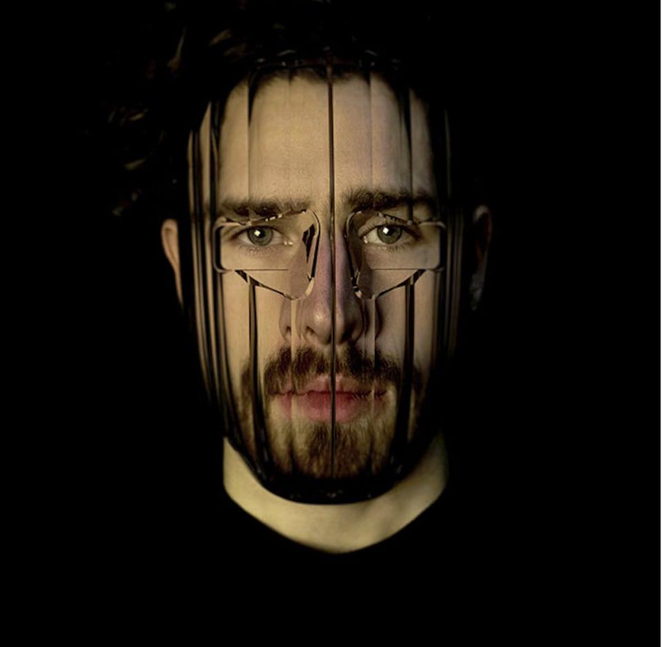 Un homme porte un masque en plastique transparent qui déforme les traits de son visage.