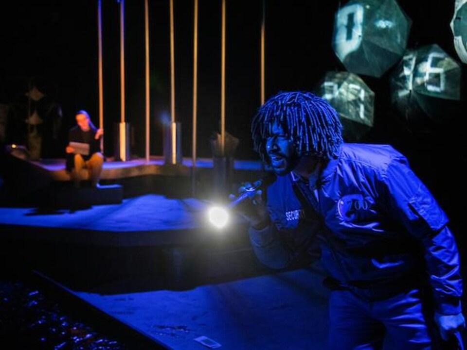 Minister Faust est en avant-plan avec une lampe de poche à la main. La scène est en arrière-plan. Quelqu'un est assis sur la scène.