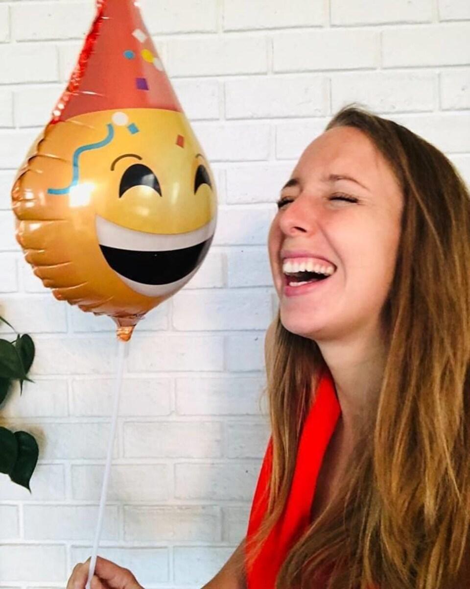 Maude Bombardier tient un ballon décoré d'un visage-sourire.