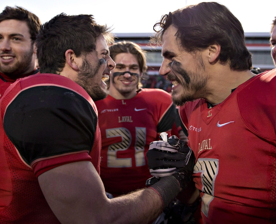Laval University Rouge et Or game MVP Maxime Boutin, left, is congratulated by team mate Jean-Philippe Bolduc as F?lix Faubert-Lussier, centre, looks on after winning over Acadia Axemen at the CIS Uteck Bowl Saturday, November 17, 2012 in Quebec City. THE CANADIAN PRESS/Jacques Boissinot