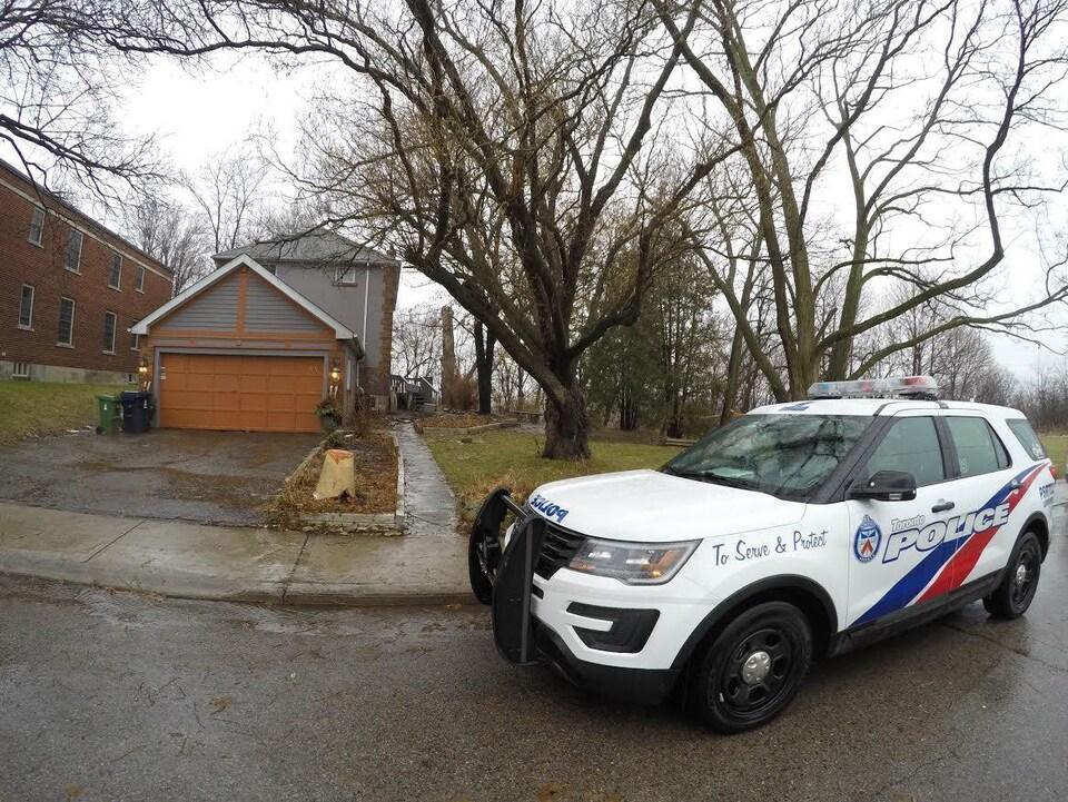 Photo d'un véhicule de police devant le garage d'une maison grise à deux étages.