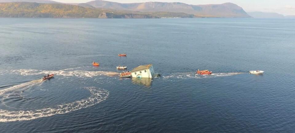 Des bateaux poussent la maison pour l'empêcher de couler.