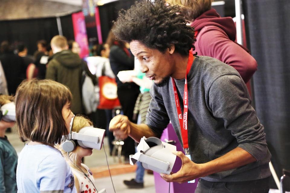 Un homme parle à une petite fille dans un salon de jeux vidéo en tenant un casque de réalité virtuelle.