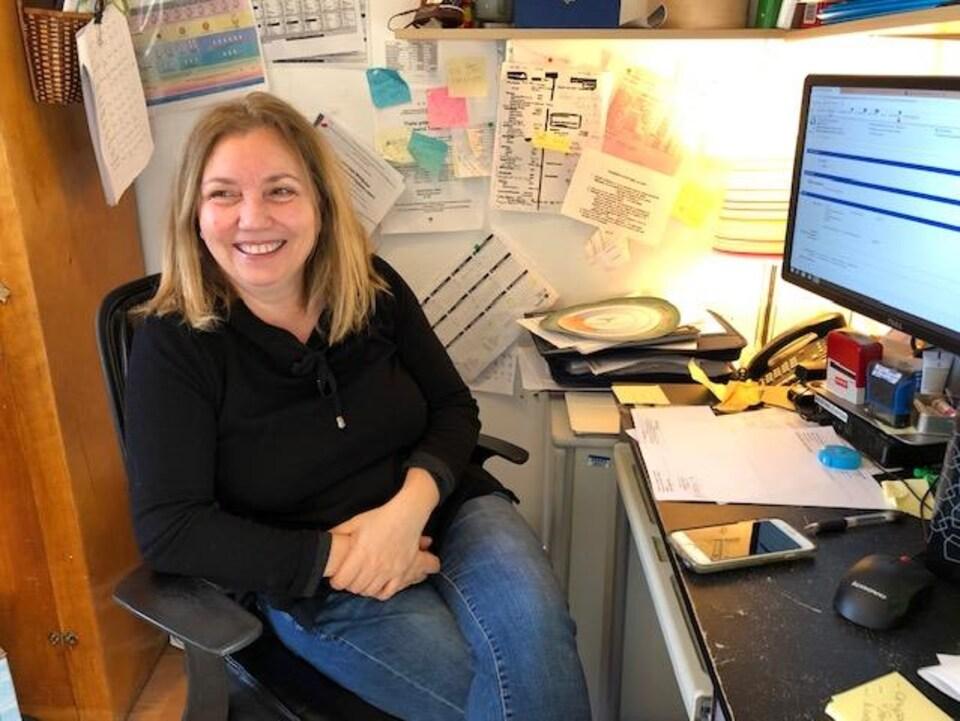 Elle assise devant son ordinateur.