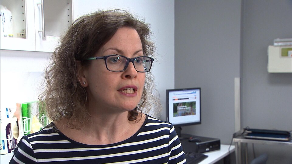 Mélanie Henderson porte des lunettes et accorde une entrevue dans son bureau.