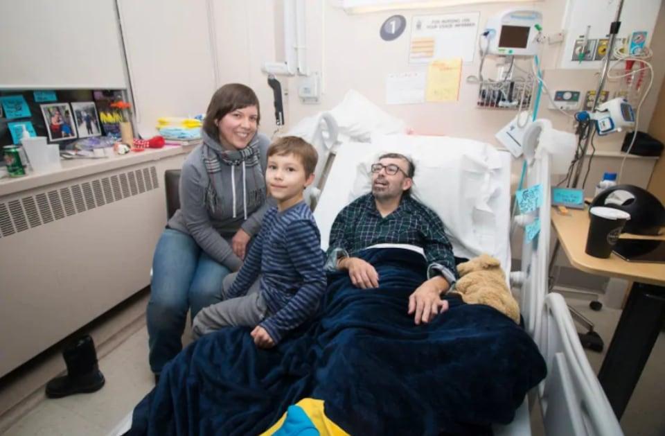 Un homme sur un lit d'hôpital avec sa femme et son fils à ses côtés.