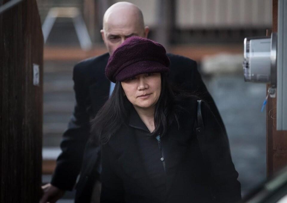 Une femme asiatique porte un chapeau et est suivie par un homme chauve.