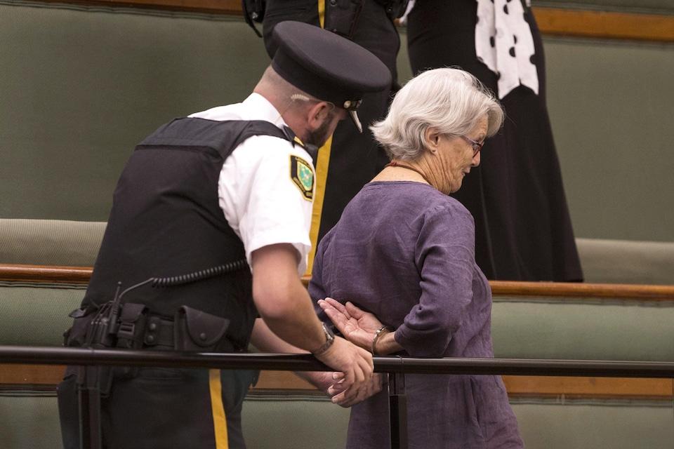 Une femme âgée aux cheveux blancs est menottée par un agent de sécurité.