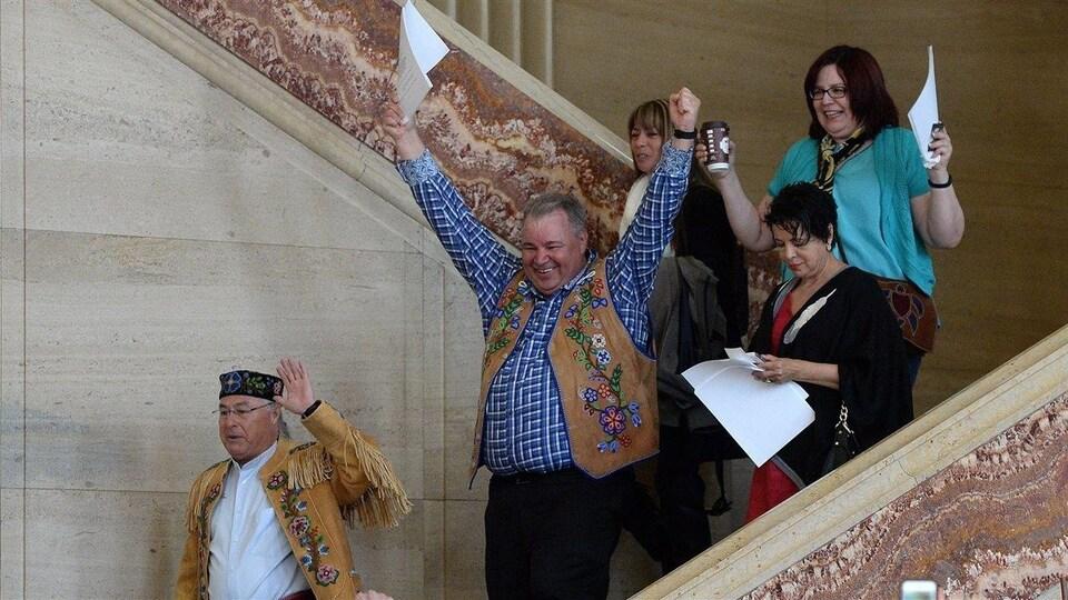 Des Métis descendent les marches de la Cour suprême en célébrant les bras dans les airs.