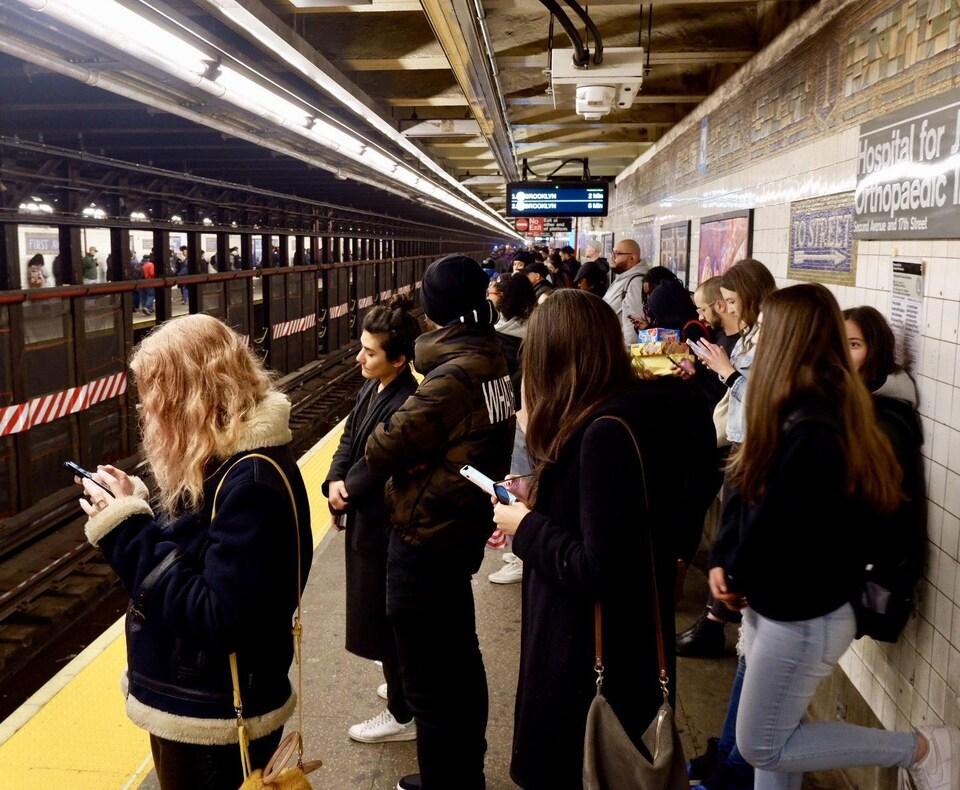 Des gens qui consultent leur téléphone intelligent attendent le métro.