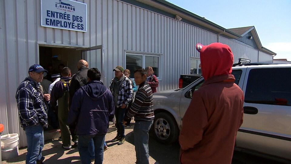 Un groupe de travailleurs devant l'entrée des employés de l'usine E. Gagnon et fils de Sainte-Thérèse-de-Gaspé.