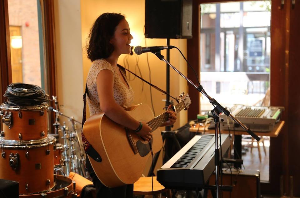 Mia Kelly, adolescente, en spectacle, en train de chanter derrière une guitare