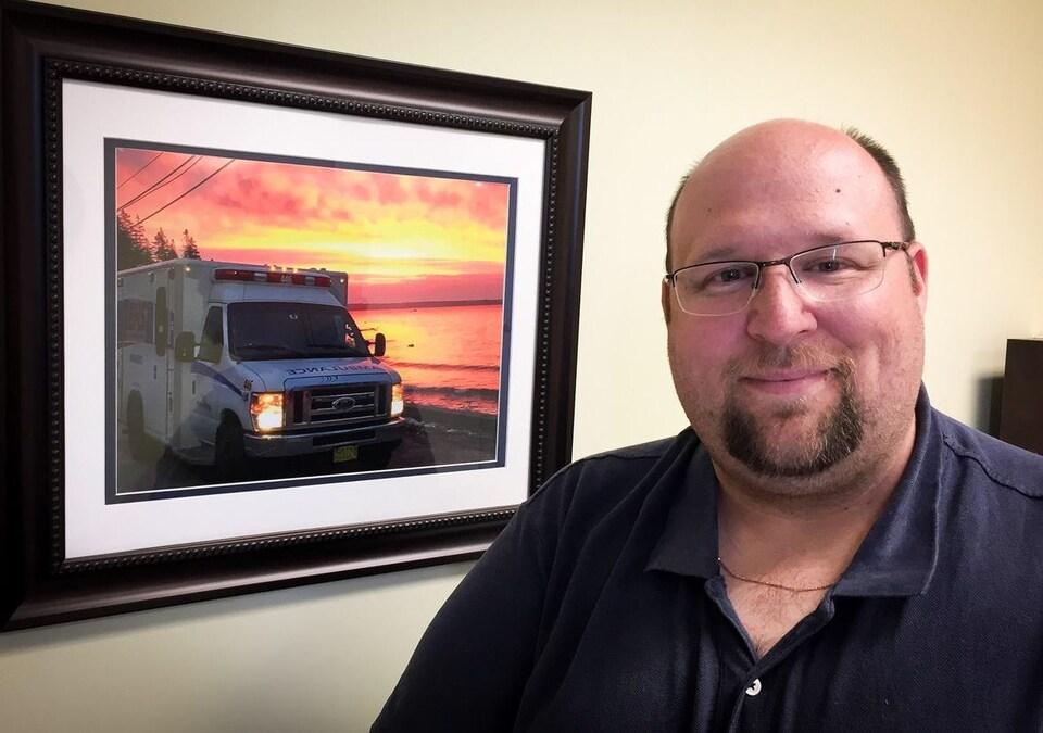 Michael Nickerson devant une photo d'une ambulance.