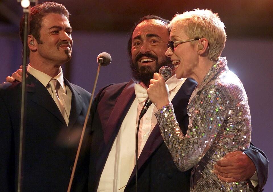 Le chanteur George Michael (à gauche) en compagnie du ténor italien Luciano Pavarotti et de la chanteuse d'Eurythmics, Annie Lennox, à l'occasion d'un concert le 6 juin 2000