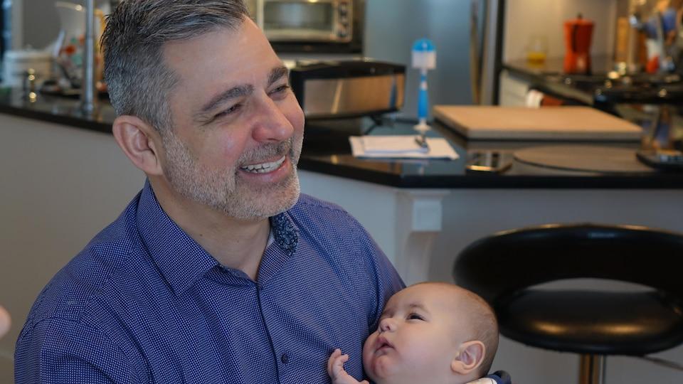 Un homme sourit en tenant son fils dans ses bras.