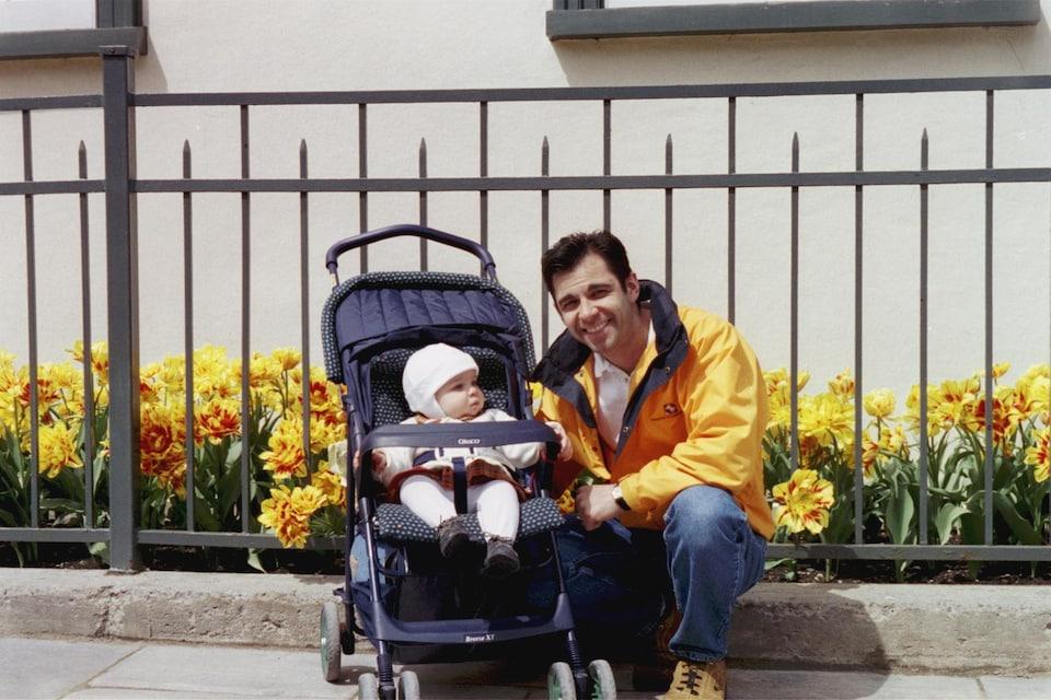 Un homme vêtu d'un imperméable jaune est accroupi à côté d'une poussette dans laquelle est assis un bébé vêtu de rose pâle.