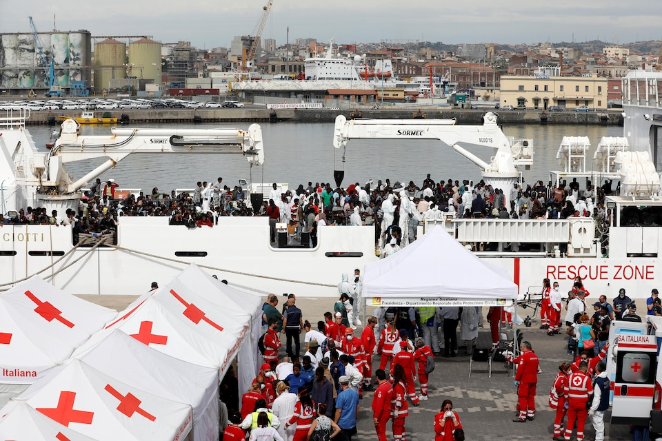 Un bateau transportant des centaines de migrants est amarré au port de Catane. Des dizaines de personnes attendent de descendre sur le pont; d'autres sont pris en charge par la Croix-Rouge après leur descente.