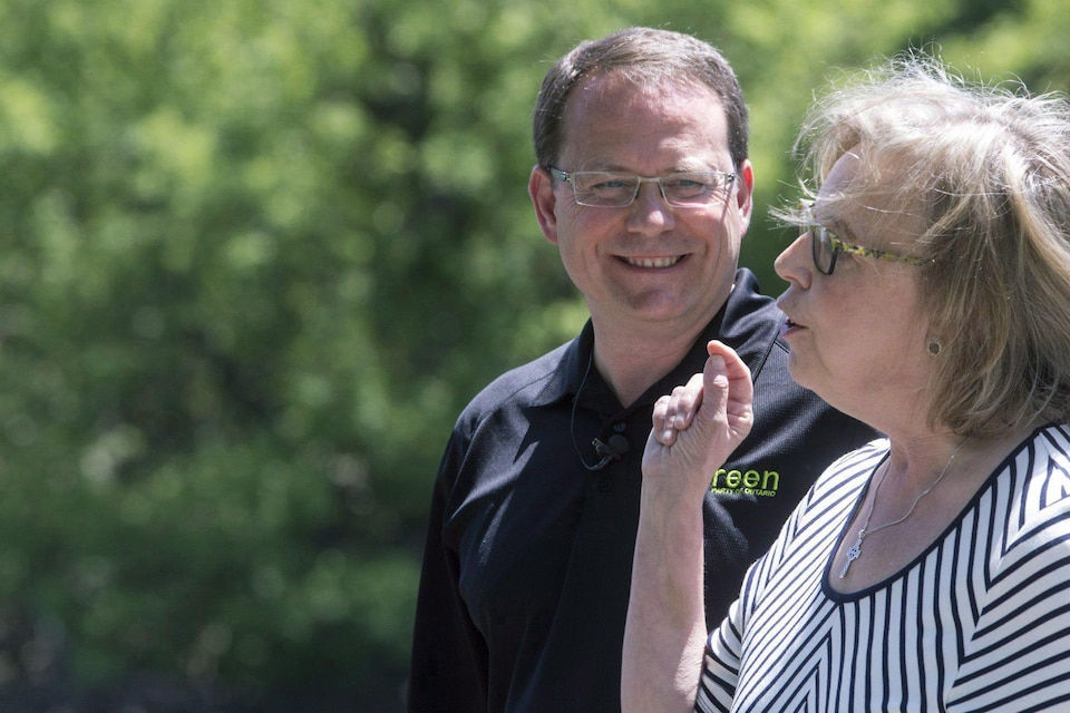 Mike Schreiner, portant un t-shirt noir, regarde Elizabeth May, vêtue d'une robe.