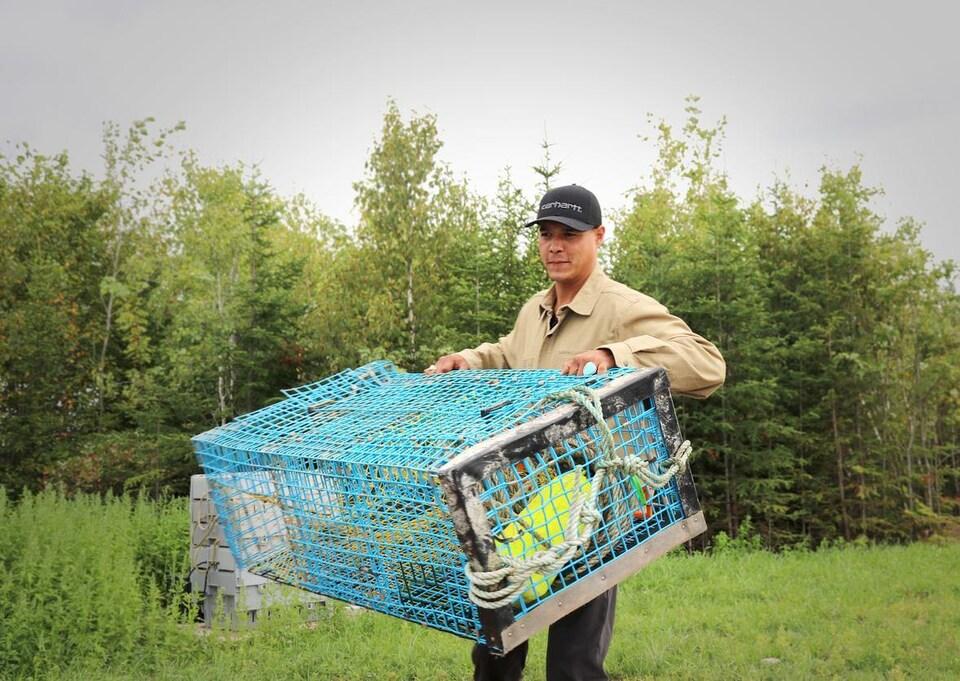Mike Stephens levant un casier à homard.