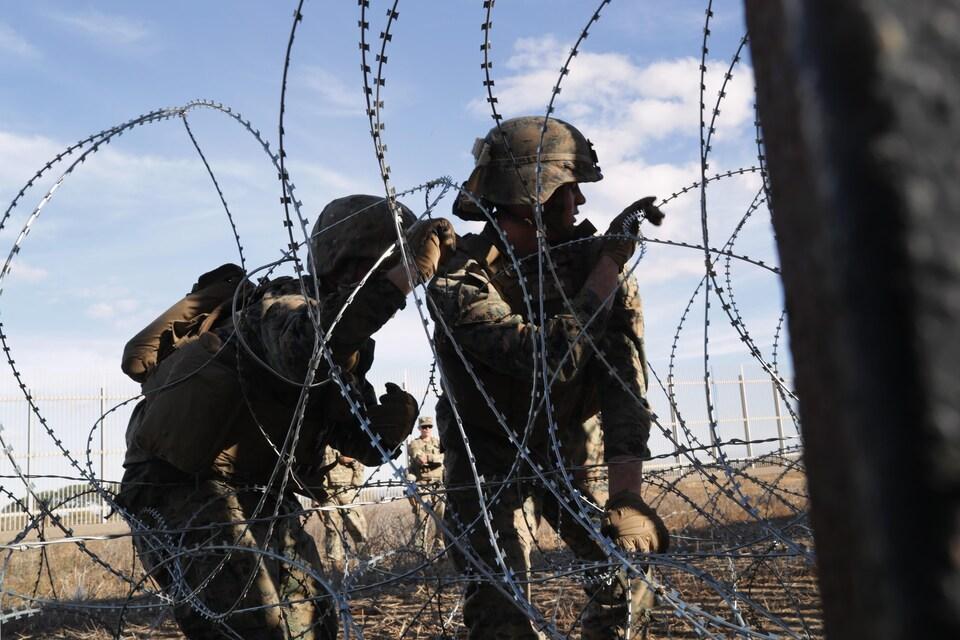 Deux soldats regardent au loin derrière des fils barbelés.