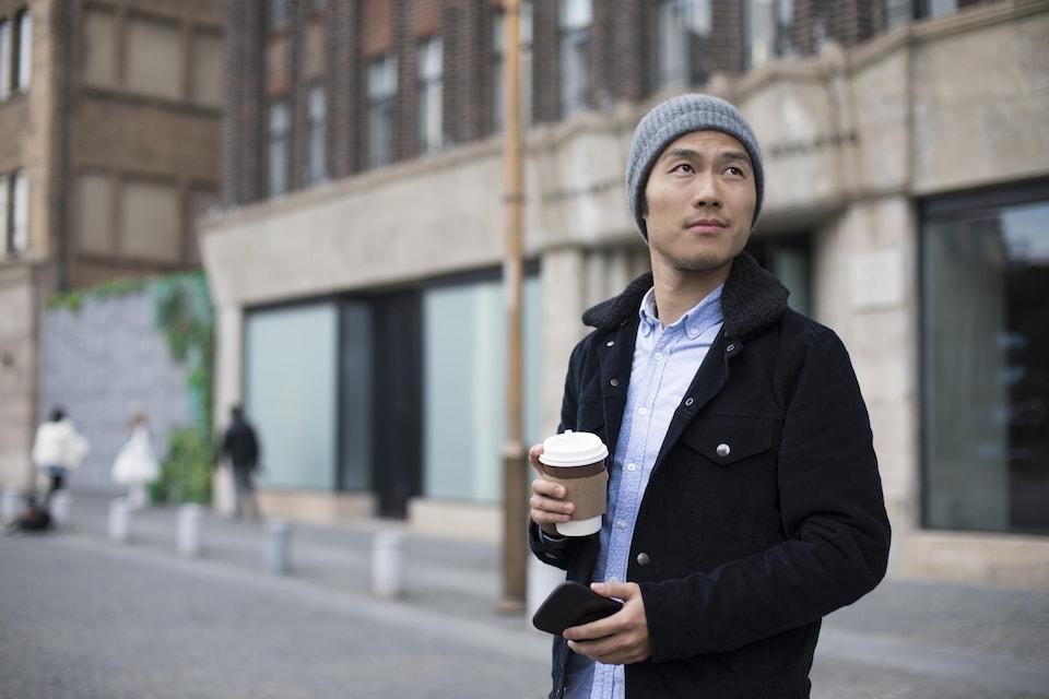 Un homme attend un Uber, café et téléphone cellulaire à la main.