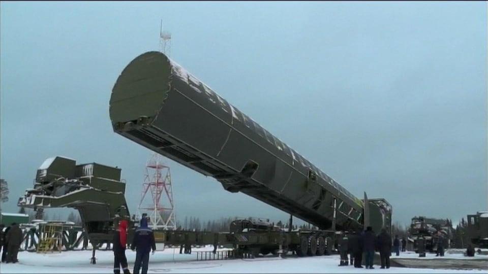 Le missile, dans un immense contenant de métal vert est transporté à l'extérieur sur un camion remorque sous le regard de personnes vêtues de manteau.