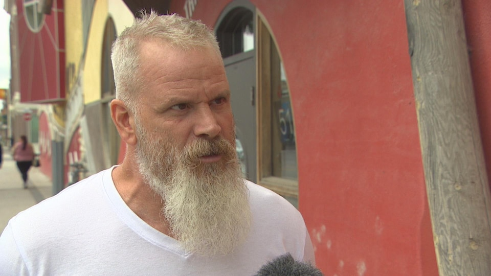 Un homme aux cheveux blancs et avec une longue barbe parle l'air sérieux dans une rue, devant une façade colorée en rouge.