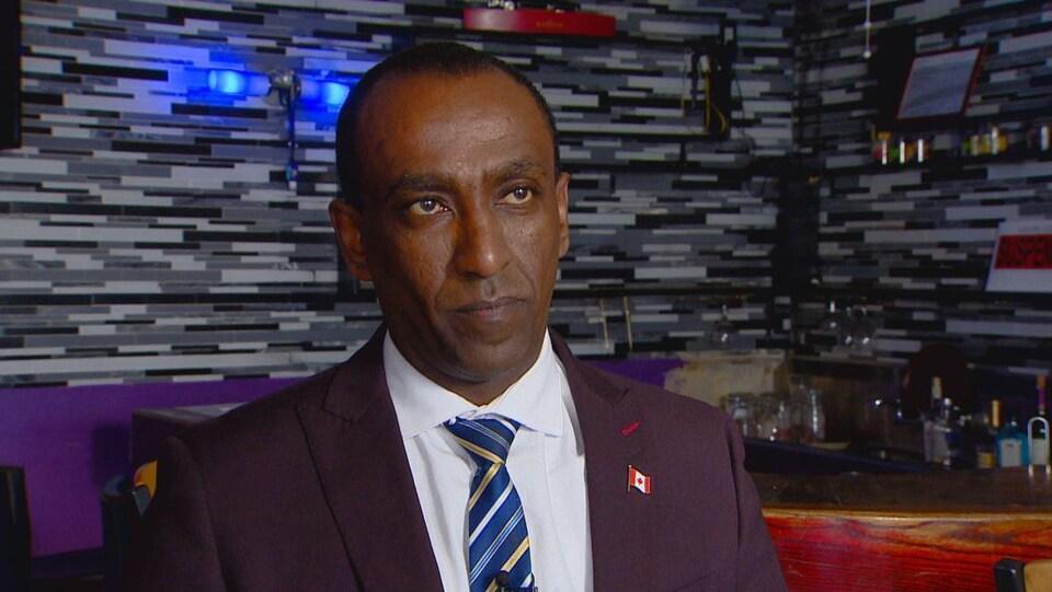 Moe Tesfay devant un bar orné de bouteilles d'alcool.