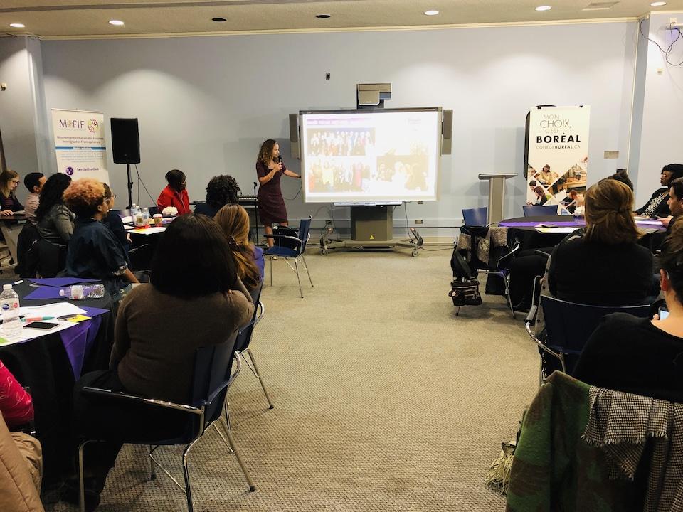 Des femmes en réunion dans une salle et une animatrice à l'avant.