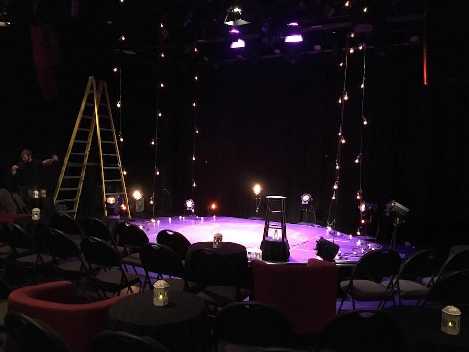 Une toute petite scène au milieu de la salle entourée de très près par des rangées de chaises.