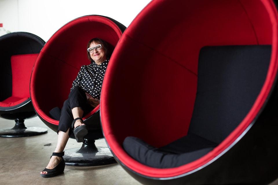 Une photo de Monique Savoie assise dans une chaise en forme de sphère.