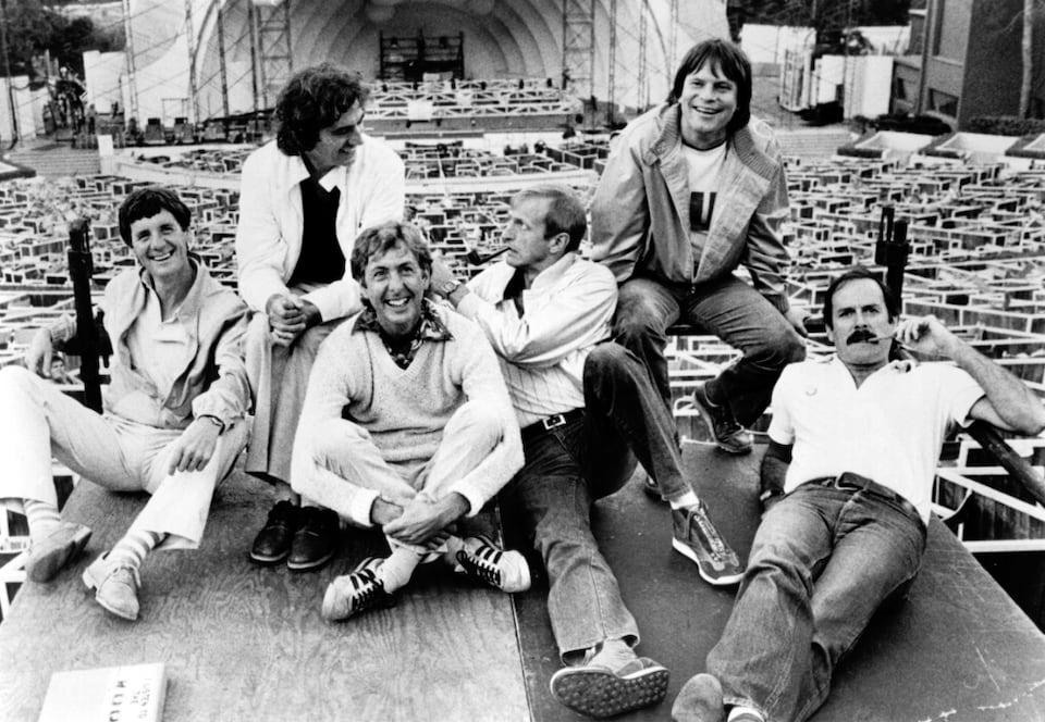 Six amis et collègues sourient à la caméra, assis dans des positions confortables.