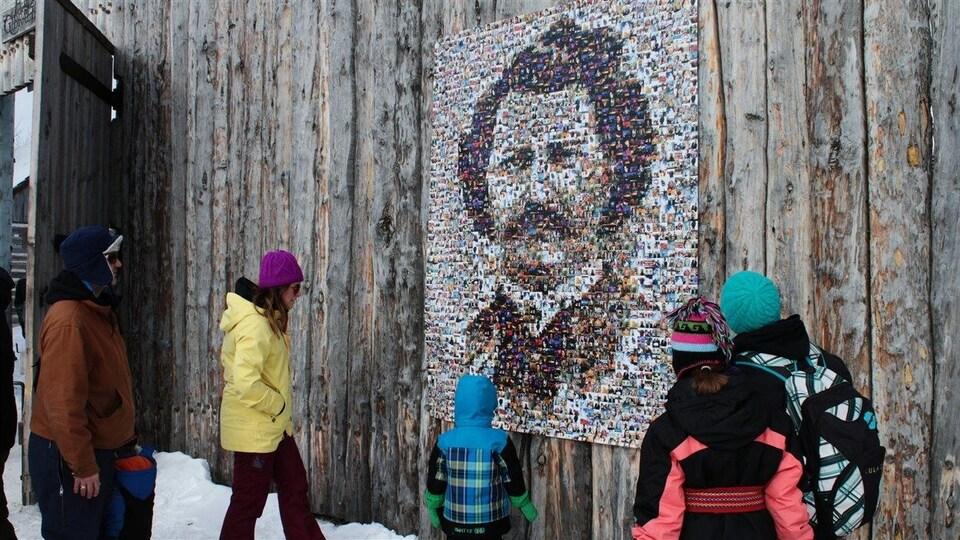 Des visiteurs observent la mosaïque Louis Riel au Festival du Voyageur.