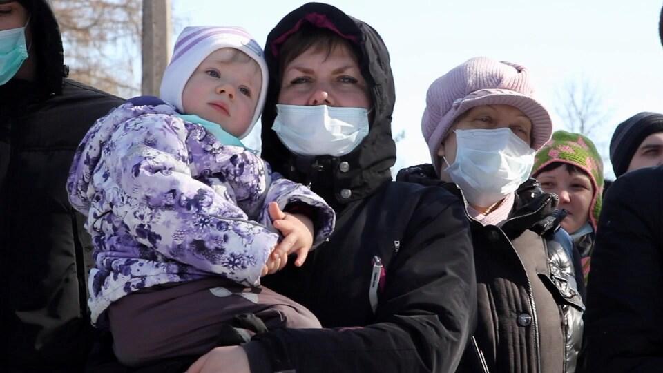 Trois femmes russes portant des masques blancs sur la bouche, se tiennent debout, l'une d'entre elles portant une jeune enfant dans ses bras.