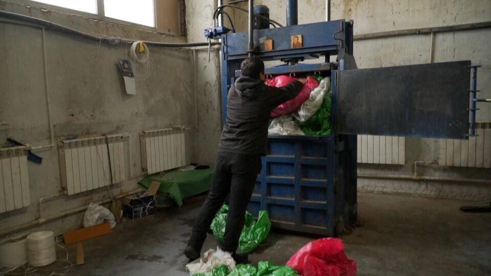 Un homme rempli un compacteur industriel de déchets en plastique dans une usine.