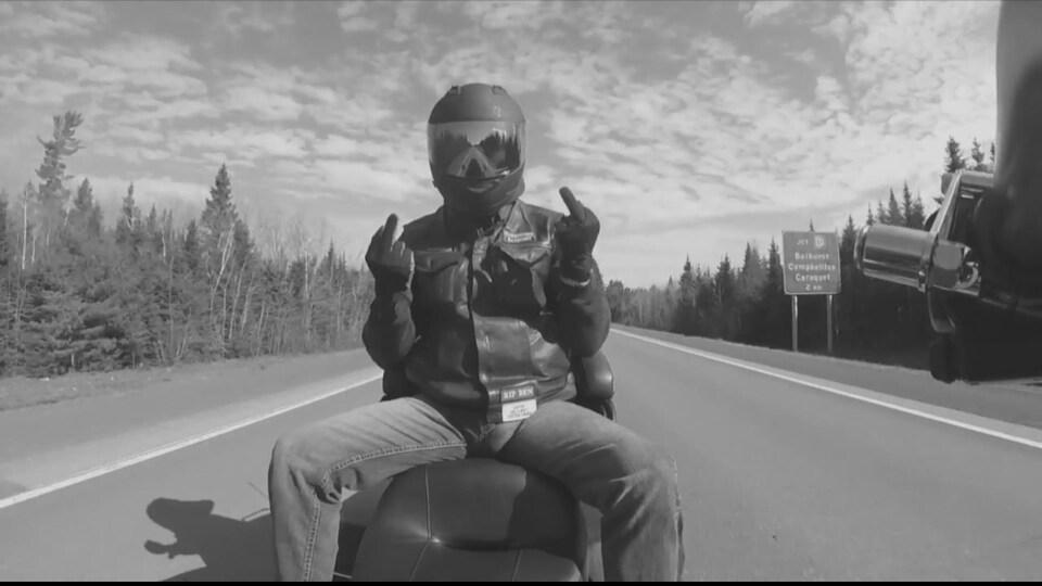 Le motard fait un geste dégradant à la caméra sur une moto. On voit à l'arrière l'affiche de Bathurst