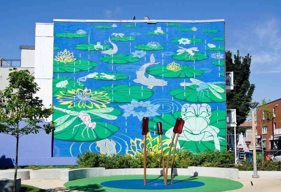 Des fleurs vertes sont peintes sur du bleu sur le mur d'un édifice.