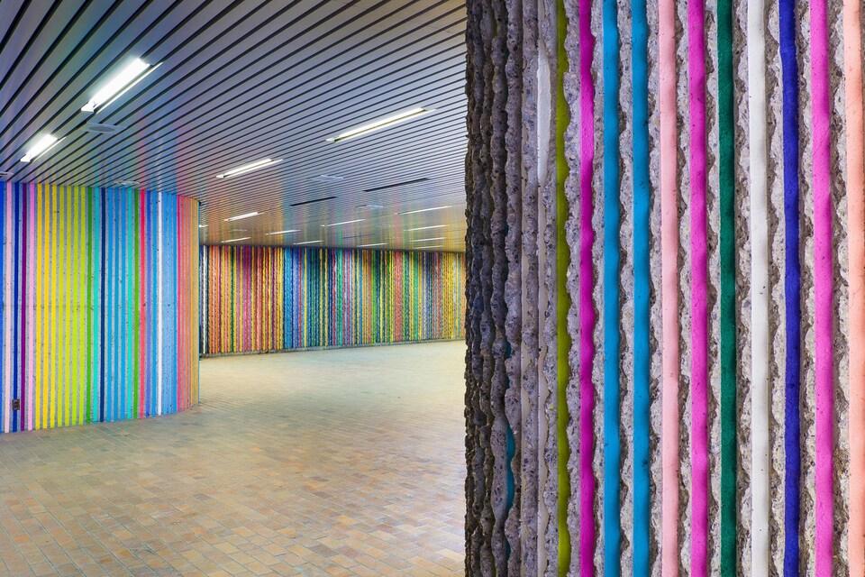 Des lignes de couleurs sont peintes sur le béton d'un tunnel.