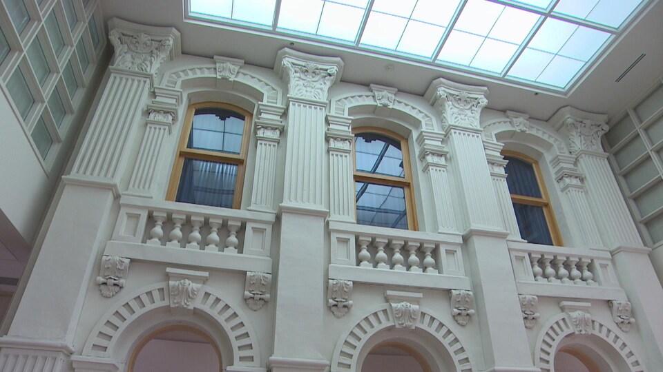 Un mur blanc avec des colonnes et des arches foisonnantes de détails architecturaux.