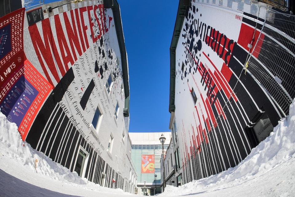 Les deux murs d'une ruelle sont couverts de mots en rouge,noir et blanc.