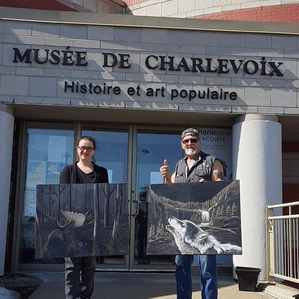 Daniel Bonneau et Nadyne Deschênes posent devant le Musée de Charlevoix avec un tableau chacun.