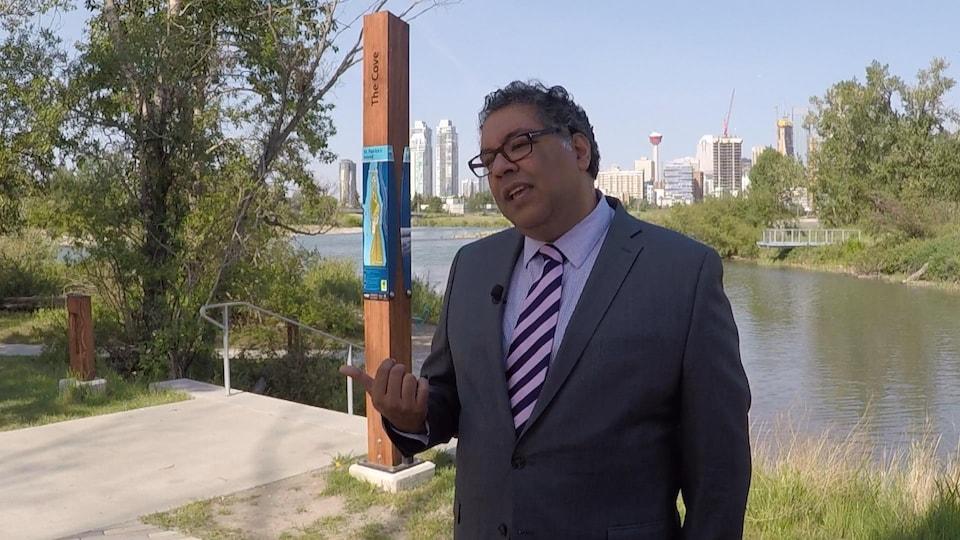 Le maire Naheed Nenshi debout sur la berge d'une rivière bordée d'arbres avec en arrière-plan la ville de Calgary.